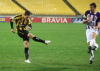 Phoenix' Troy Hearfield rifles a cross between Naum Sekulovski's legs during the A-League football match between Wellington Phoenix and Perth Glory at Westpac Stadium, Wellington, New Zealand on Sunday, 16 August 2009. Photo: Dave Lintott / lintottphoto.co.nz