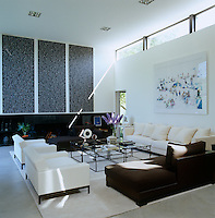 A photograph by Masimo Vitali hangs above a white Wanda sofa by Promemoria in this black and white living room