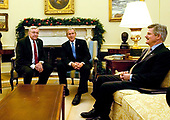 Washington, D.C. - November 30, 2005 -- United States President George W. Bush, center, meets Jim Mueller, National Commander-in-Chief of the Veterans of Foreign Wars (VFW), left, in the Oval Office in the White House on November 30, 2005.  Jim Nicholson, Secretary for Veterans Affairs looks on from right.<br /> Credit: Ron Sachs - Pool via CNP