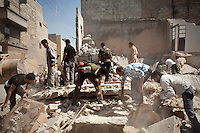 Free Syrian Army (FSA) fighters and civilians search for bodies or wounded amongst the rubble of a residential home destroyed by two bombs dropped from Syrian Airforce fighter jets that were targeting the neighbouring FSA command centre in Aleppo. Eleven civilians from two families died including at least four children.