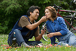 Couple having picnic, man feeding woman strawberry