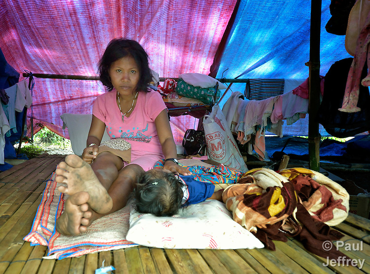 A woman and her child, residents of the indigenous village of San Fernando, on the southern Philippines island of Mindanao, fled their home on March 14, 2012, shortly after the March 5 assassination of Jimmy Liguyon, their baranguay captain. Liguyon was killed by a paramilitary squad led by Aldy Salusad, which was angered by Liguyon's refusal to sign papers ceding the community's land to a large mining company. Convinced they were also in danger from Salusad and his military allies, they and almost 200 other community members fled to the provincial capital of Malaybalay, where they have set up temporary shelters on the grass in front of provincial offices. They promise not to leave until there is justice in the killing of Liguyon..