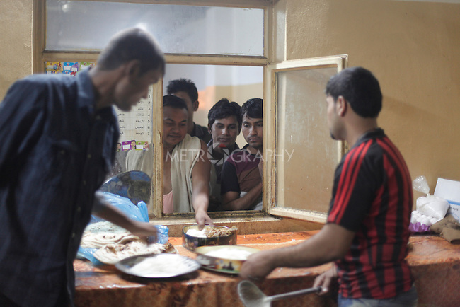 10/10/2014 -- Kirkuk, Iraq -- Bangladeshi workers get dinner in the garage where they live in Kornish street.