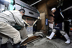 A brewery staff hand collects rice that has been steamed at the beginning of the brewing process of sake, a wine-like beverage fermented from rice, water, yeast and a starch-killing mold called koji-kin, at a sake brewery in Kyoto, Japan. More than 1,200 sake breweries exist in Japan, though falling domestic consumption has lead some to look to  overseas markets...Photographer: Robert Gilhooly