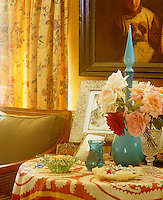 Amongst floral chintz curtains and a posy of pale pink roses a clear note of turquoise sounds from a bottle made of coloured glass