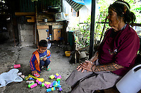PHILIPPINES, Cordillera highlands, Bontoc, Samoki village, Igorot people, Samoki tribe, old woman with tattoo and snake skeleton in hair take cares of her grandchildren as the parents working overseas / PHILIPPINEN, Cordilleras, Bontoc, Samuki Dorf, Igorot Volksgruppe, Samoki Clan, alte Frau Pingao Chinalpan, geb. 1936, kuemmert sich um ihre Enkel, die Eltern arbeiten im Ausland