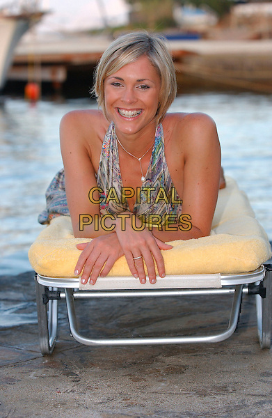 JENNI FALCONER.Photoshoot.30th May 2002.Ref:J Barnard.half length lying down sunbed mattress multicoloured patterned flowery floral halterneck silk satin dress tan tanned skin sea water.www.capitalpictures.com.sales@capitalpictures.com.©Capital Pictures