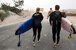 Long Beach Island, NJ - June 30, 2013 : Lila Walerych, from New York with surfing instructor Eric Leonard head to Brighton Beach for a surf lesson on Long Beach Island, NJ on June 30, 2013. People are returning to the beaches for the summer after recovery efforts post Superstorm Sandy.