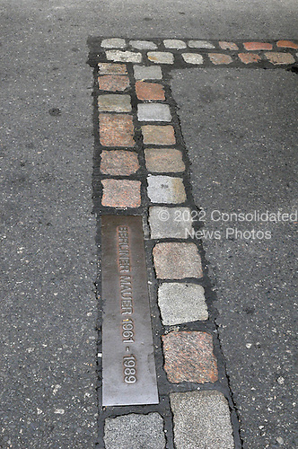 "Berlin, Germany - August 11, 2009 -- Bricks and a bronze plaque mark the path of the Berlin Wall near ""Checkpoint Charlie"" in Berlin, Germany on Tuesday, August 11, 2009..Credit: Ron Sachs / CNP"