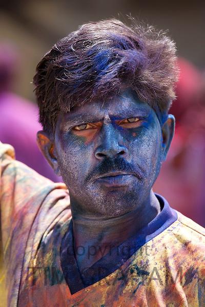 Indian man celebrating annual Hindu Holi festival of colours smeared with powder paints in Mumbai, formerly Bombay, Maharashtra, India