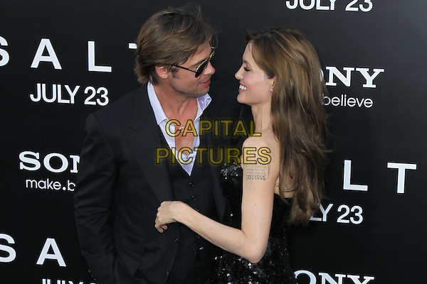"BRAD PITT & ANGELINA JOLIE.Arrivals to the World Premiere of Sony Pictures' ""Salt"" at Grauman's Chinese Theatre. Los Angeles, CA, USA. .July 19th, 2010.half length black white shirt aviators suit strapless sequined sequin black dress  couple sunglasses shades tattoo profile .CAP/CEL.©CelPh/Capital Pictures..."