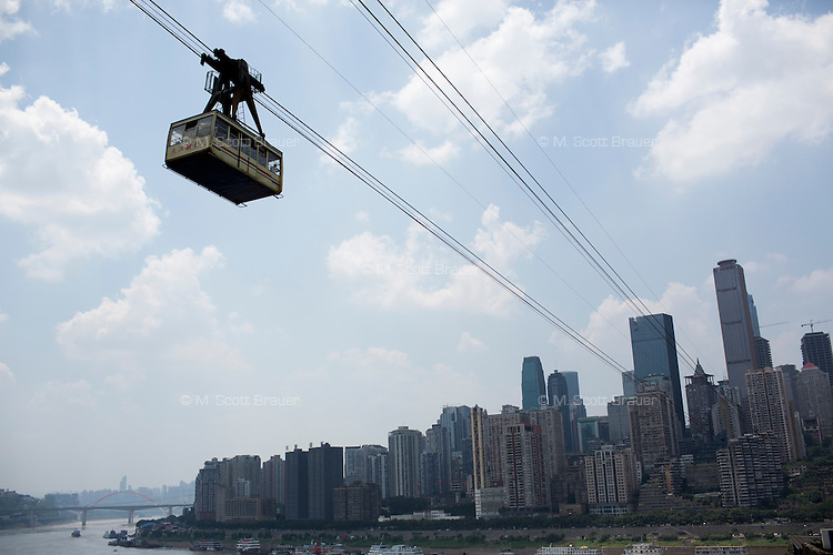 A Chongqing Cable Car gondola hangs above the Yangtze River with buildings of the Yuzhong District visible in the distance in Chongqing, China.