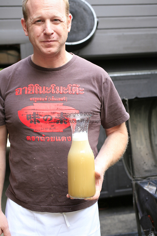 Pok Pok Restaurant, owner Andy Ricker holding a liter of freshly squeezed sugar cane juice.