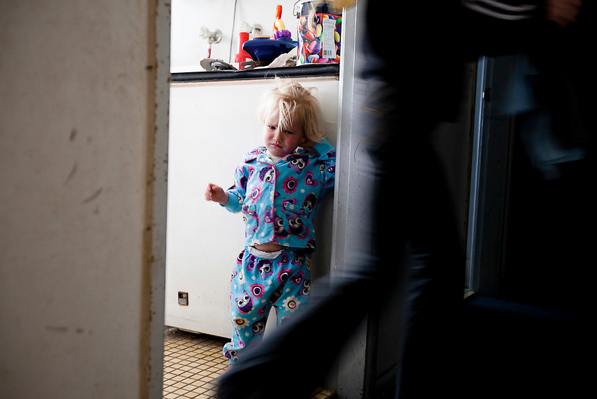 An unnamed girl watches her mother walk by in a housing commission flat in the suburb of Whalan, Mt Druitt, Western Sydney, August 2010. Children in suburbs on the fringes of Australia's cities face increased risk of social disadvantage, according to University of Canberra researchers. Photo: Ed Giles.