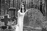 A teenage girl in a wedding dress standing in a graveyard behind a grave