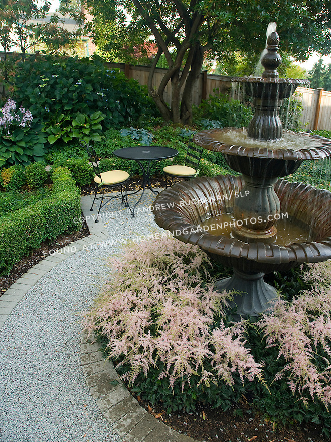 detail of a central water feature surrounded by astilbe within a formal backyard garden, edged with roses, framed by boxwood, and paved with gravel , sits in the quiet late afternoon light behind a home in a suburban community east of Seattle