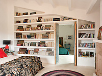 Wall to wall bookshelves built into the partition wall between two bedrooms provide lots of storage space