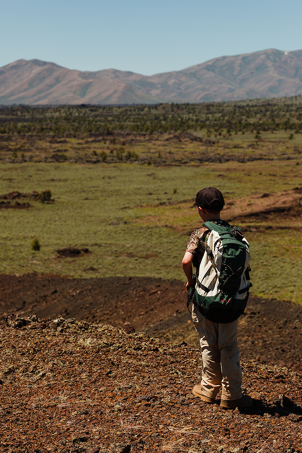 Young boy looks out at the hills of Craters of the Moon National Preserve.