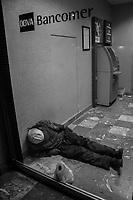 Un indigente duerme en el interior de el cajero Bancomer dedito al frito en el exterior,  en el bulevar Rodriguez de Hermosillo. Viste de gorra y lleva con sigo una  cerveza Caguama  en una bolsa de plástico.