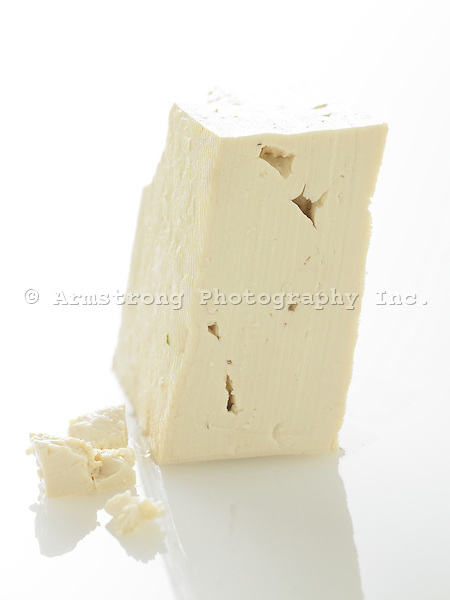 A large chunk of unseasoned tofu on a white background.