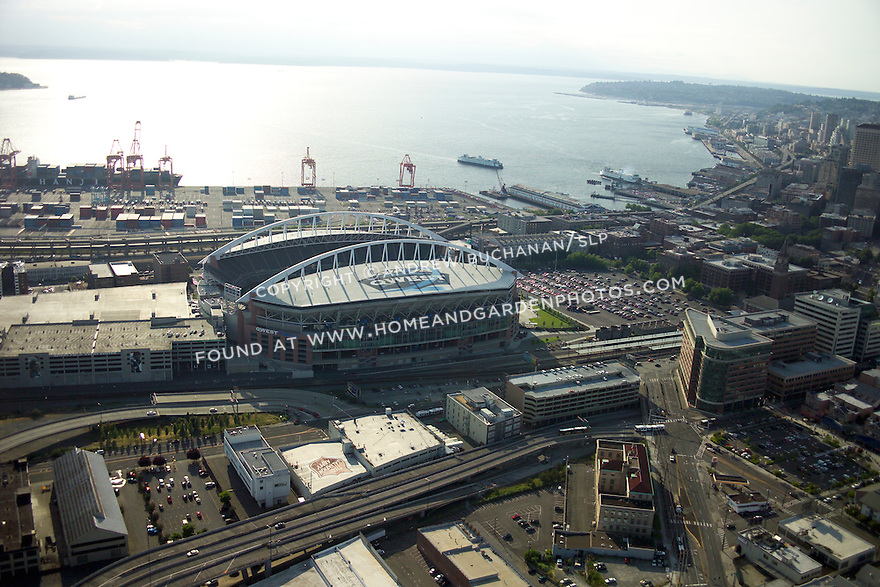 A late afternoon aerial view of Qwest Field, home stadium of the Seattle Seahawks football team of the National Football League, NFL, and the Seattle Sounders of Major League Soccer, MLS, with the Qwest Field sign clearly visible, the Port of Seattle just behind, a ferry approaching the dock, and the buildings of downtown stretching away along the waterfront of Elliott Bay and Puget Sound beyond