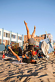 USA, Los Angeles, a couple doing yoga together on the sand near the Venice Boardwalk