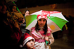 IRAQ, SULAIMANIYAH:  A girl and her brother wearing Christmas hats take shelter from the rain under a flag decorated with the colors of the Kurdish flag...Revelers brought in the new year all across Kurdistan with shows of fireworks and enormous street parties...Photo by Metrography
