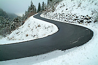 Winding road through a snow-covered valley, Chabanon, French Alps, France.