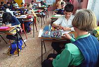 Un'insegnante di sostegno con un alunno in una classe di scuola elementare. Milano, 3 settembre, 2003<br /> <br /> Support teacher with a pupil in a classroom of  primary School. Milan, September 3, 2003