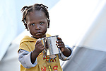 A young survivor of Haiti's devastating January 12 earthquake drinks water outside her family's tent in a displaced person's camp in the Belair section of Port-au-Prince.
