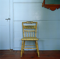 A pretty, antique chair painted with a floral motif is placed against a duck-egg blue wall