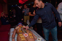 Guests eat sushi that is served on the bodies of naked women following japanese traditions in a club in downtown Budapest, Hungary on September 23, 2011. ATTILA VOLGYI