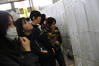 People look at evacuation lists in the town of Natori, hoping to see the names of missing relatives.  The Tsunami devastated ahe entire pacifc coastline of Japan after the earthquake and tsunami devastated the area Sendai, Japan.<br /><br />photo by Richard Jones/ sinopix