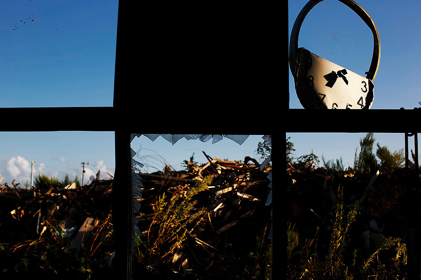 A twisted clock, spider's webs and debris are seen from inside damaged primary school at the tsunami destroyed coastal area of the evacuated town of Namie in Fukushima prefecture only some 6 kilometers from crippled Daiichi power plant September 23, 2013. A total of 160,000 people had been forced to leave their homes around Daiichi plant after the government ordered the evacuation following the nuclear disaster in March 2011.  REUTERS/Damir Sagolj (JAPAN)