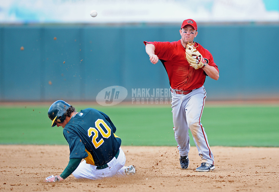 Mar. 19, 2012; Phoenix, AZ, USA; Arizona Diamondbacks second baseman Aaron Hill throws to first base to complete the double play after forcing out Oakland Athletics base runner Josh Donaldson in the fourth inning during a spring training game at Phoenix Municipal Stadium.  Mandatory Credit: Mark J. Rebilas-