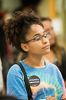"""College student Katherine Cabral, 20, of Chelsea, Mass., listens as Ayanna Pressley speaks at an event put on by Chelsea Black Community at the Chelsea Senior Center in Chelsea, Massachusetts, USA, on Wed., June 27, 2018. Pressley is running in the Democratic primary Massachusetts 7th Congressional District against incumbent Mike Capuano. Pressley is currently serving as a member of the Boston City Council, and is the first woman of color elected to the Council. Cabral is a volunteer for Pressley's campaign and says she will soon be canvassing for the candidate. """"I realized as a youth, I have a power to make a change,"""" Cabral said."""