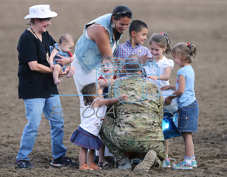 Nevada Army National Guard Chief Warrant Officer Glen Spadin surprises his family in front of nearly 9,000 people at the Reno Rodeo in Reno, Nev. on Friday, June 19, 2015. Spadin returned after a year in Afghanistan to surprise his six children. His mom Gaile, is at left, his wife Maja, center, and their children Faith, 6-months, Rebecca, 2, Sarah, 4, Mark, 9, Rachel, 7, and Hannah, 5. <br /> Photo by Cathleen Allison