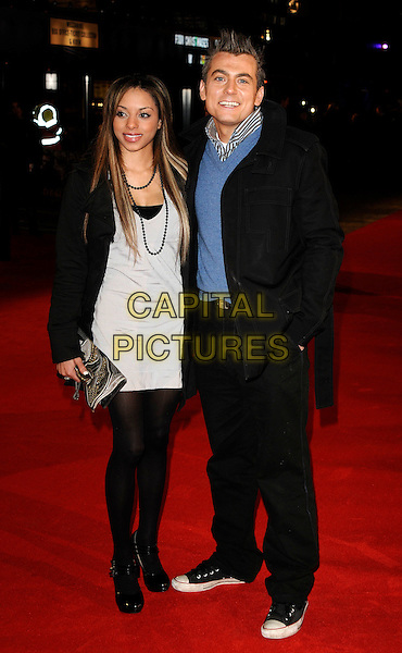 "GUEST & PAUL DANAN.The European Film Premiere of ""Defiance"" at Odeon Leicester Square, London, England. .January 6th 2009. .full length black tights suit blue shirt grey gray dress clutch bag silver .CAP/CAN.©Can Nguyen/Capital Pictures."
