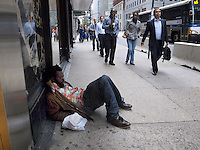 USA. New York City. A black afro-american homeless man sleeps on the pavement on Madison Avenue. Crowds walking in Midtown Manhattan. Lunch hour. MTA public city bus. 21.10.2011 © 2011 Didier Ruef