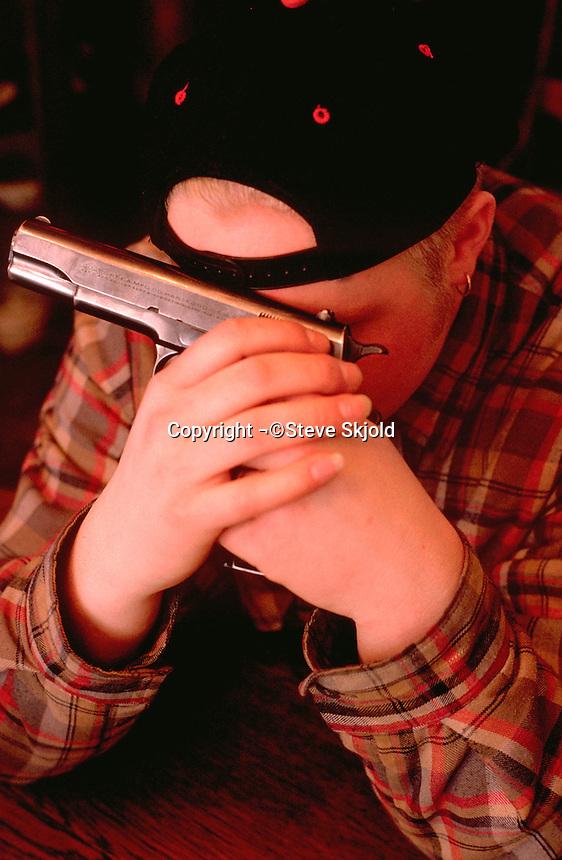 Man age 20 holding Colt .45 pistol against face over eyes.  St Paul Minnesota USA