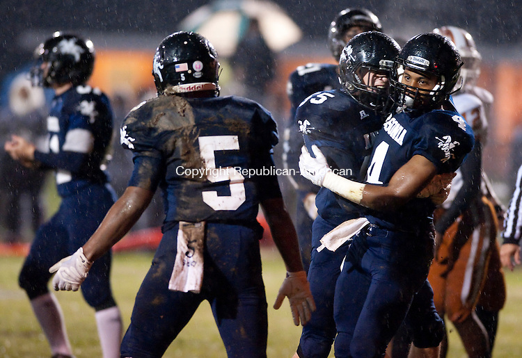 ANSONIA, CT--- -120115JS06--Ansonia's Tajik Bagle (4) is congratulated by teammate Keith Zdep (55) after scoring a touchdown during their Class S Quarterfinal game against Capital Prep Tuesday at Jarvis Stadium in Ansonia. <br /> Jim Shannon Republican-American