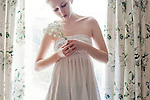 Young girl wearing a white dress holding a vase, whith pale skin, looking away from the camera, with floral curtain and window background.
