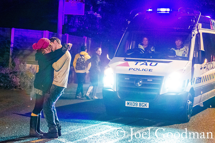 © Joel Goodman - 07973 332324 . 30/06/2012 . Manchester , UK . A couple kiss and embrace in the middle of the road , obstructing a police van with blue lights flashing . Crowds pour out of Heaton Park on to surrounding streets after the end of the Stone Roses Second Coming reunion gig . Photo credit : Joel Goodman