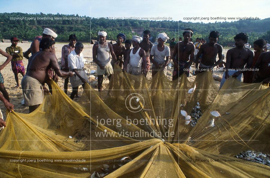 INDIA Kerala Kovalam, coast fisherman with net at Beach / INDIEN Kerala, Kuestenfischer leeren die Netze am Strand , ihre Einkünfte sind zunehmend durch internationale Fangflotte bedroht