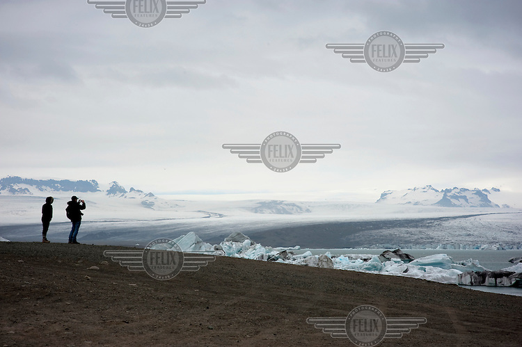 Visitors photograph icebergs floating in the waters of the Jokulsarlon Glacial River Lagoon at the terminus of the Breidamerkurjoekull Glacier, a side arm of Vatnajokull, Europe's largest ice cap and glacier which covers over 8% of Iceland.