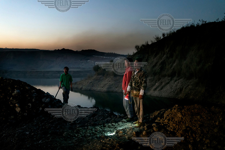 Freelance miners wait to scavenge for jade rocks in the discarded tailings from Hmaw Si Sar Mine.