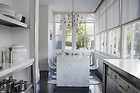 A white carrara marble table dominates the kitchen area which is lined with windows