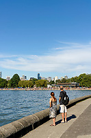 A man and woman enjoying the view on the Kitsilano seawall path with Kitsilano Beach and English Bay in back, Vancouver, British Columbia, Canada