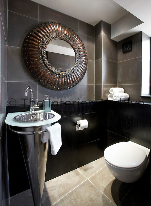 A grey tiled bathroom with a round metal mirror above a conical shaped washbasin.