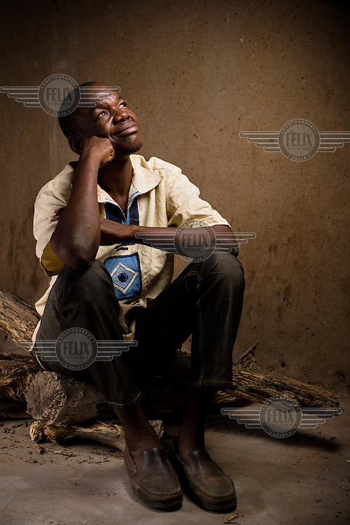When Francis Pii Kugbila became mentally unwell in 2009, his brothers took him to a traditional healer who forced his leg through a hole in a heavy length of tree trunk and pinned it in place, fashioning a crude restraint. Kugbila spent two years restrained in this manner, naked in this bare concrete room where he ate, slept and relieved himself. In late 2010 he came to the attention of mental health advocacy NGO, BasicNeeds, who arranged for him to receive appropriate treatment and negotiated for his release. Now fully recovered, pictured here on 28 January 2013, Kugbila has been able to rebuild his family life and return to his profession as a teacher. He is seated atop the weathered remains of the log that was used to restrain him.